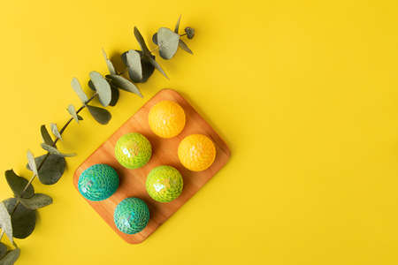 Composition fro the eucalyptus branch and glossy easter eegs in the wooden tray, Creative layout with copy space.Trendy yellow background.Horizontal banner.