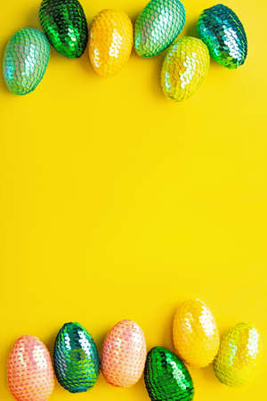 Frame made from multicolored glossy easter eggs.Trendy yellow background.Creative layout with copy space.Vertical photography. 版權商用圖片