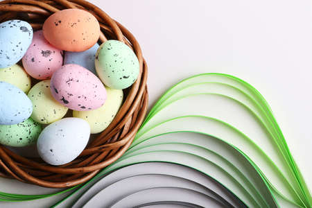 Colorful easter eggs in the rattan nest on the pastel grey background.Green paper like grass under it.Creative layout with copy space.