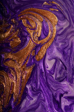 Beautiful purple and gold stains of liquid nail polish,fluid art technique.Shimmer marble background.Liquid stripy paint texture.Nail laquer flow modern backdrop.Minimalistic concept.Copy space.