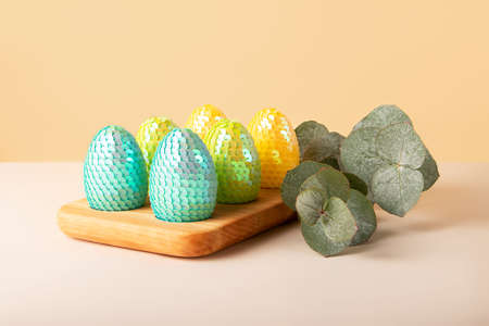 Composition from the eucalyptus branch and glossy easter eggs in the wooden tray.Creative greeting card with copy space.Trendy isometric pastel background.Horizontal banner.