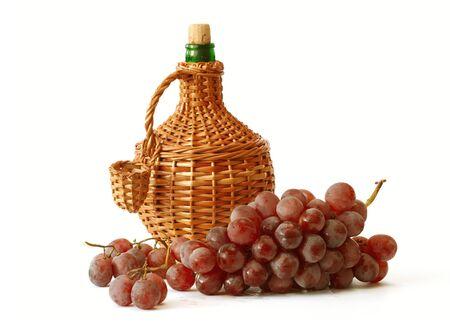 Grappe de raisin rouge avec une bouteille de vin de wicker