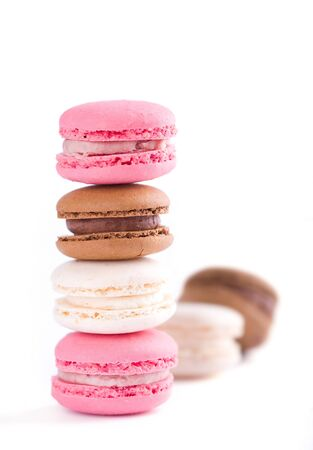 Stack of colorful french macaroons on white background