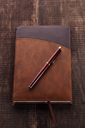 clerical: The notebook and pen on wood and board