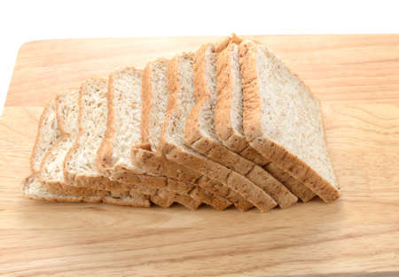 Slices of bran bread on wooden board isolated on white background