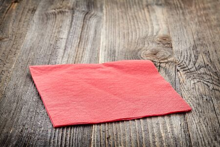 napkin: Red paper napkin on wooden table