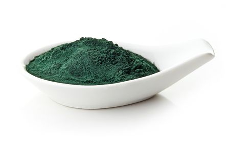 Spirulina powder in white porcelain spoon on white background, isolated Reklamní fotografie