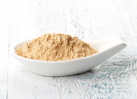 maca: Maca powder in white porcelain spoon on white wooden table