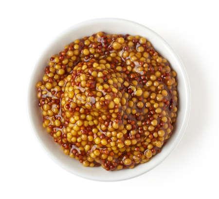 wholegrain mustard: Bowl of full wholegrain mustard on white background, top view
