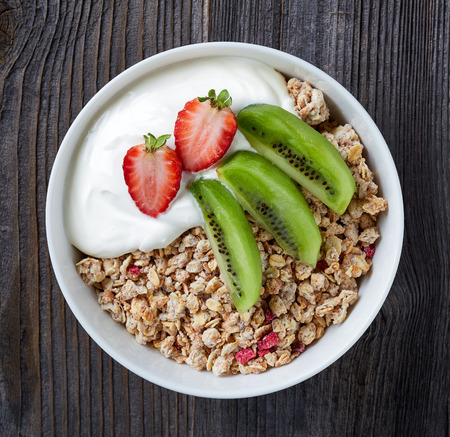 breakfast bowl: Healthy breakfast, bowl of granola with yogurt and fresh fruits on wooden table, top view Stock Photo