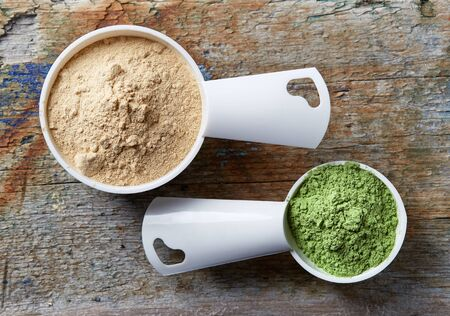 maca: Measuring scoops of maca and barley or wheat grass powders on wooden table Stock Photo