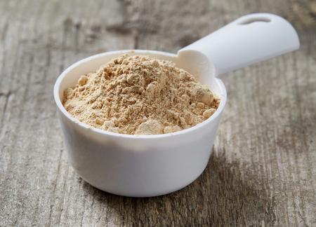 maca: Measuring scoop of maca powder on wooden table