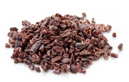 Heap of cacao nibs, isolated on white background