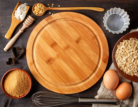 Baking background with cutting board, eggs, sugar, flour and various tools, top view Standard-Bild