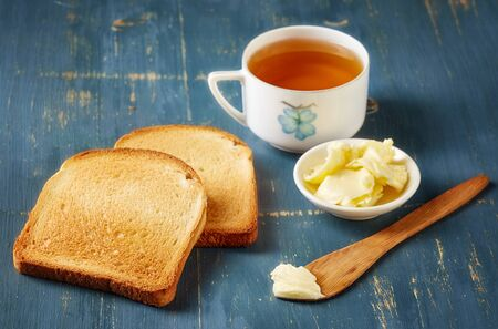 wheat toast: Slices of toast bread, butter and tea on blue wooden table