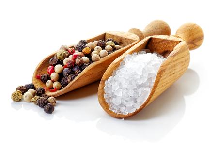 sal: Sal y pimienta en las palas de madera en el fondo blanco