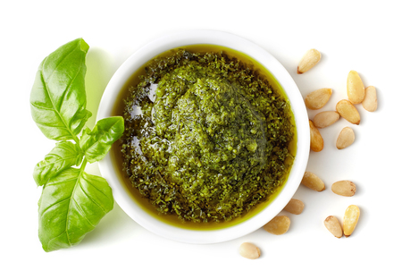 Green pesto sauce, pine nuts and basil isolated on white background, top view