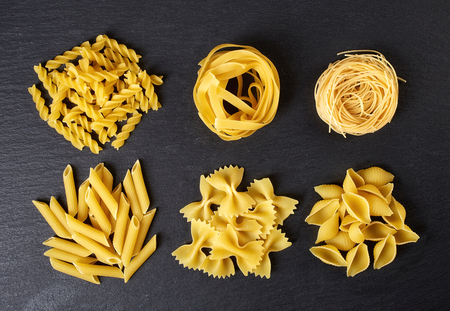 Various types of pasta on black stone table, top view