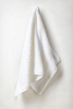White spa towel hanging on white bathroom wall