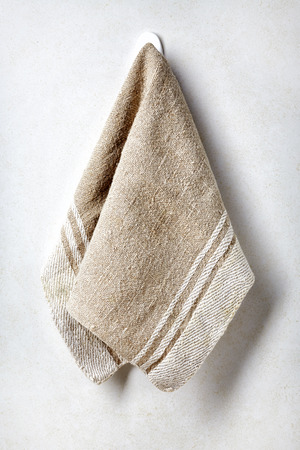 Beige linnen towel hanging on white bathroom wall background