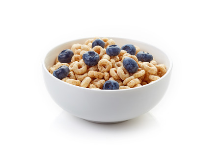 Bowl of whole grain cheerios cereal with blueberries isolated on white background Stock Photo