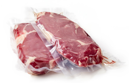 Vacuum sealed fresh beef steak for sous vide cooking isolated on white background