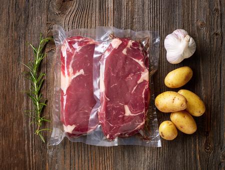 나무 테이블에 sous vide 요리를위한 신선한 쇠고기 스테이크 스톡 콘텐츠