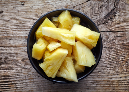 chunks: Bowl of canned pineapple chunks on wooden table, top view Stock Photo