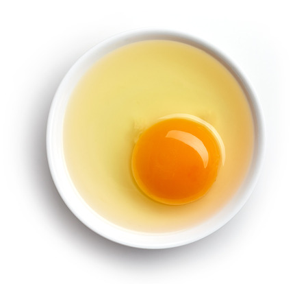 Bowl of egg yolk isolated on white background, top view