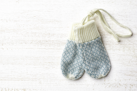 Blue baby gloves on white wooden background, top view