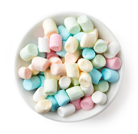 Colorful marshmallows in white bowl isolated on white background, top view