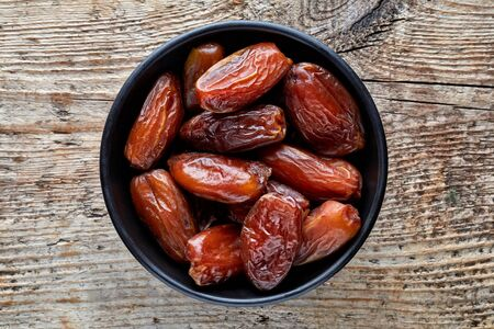 deglet: Bowl of pitted dates on wooden background, top view