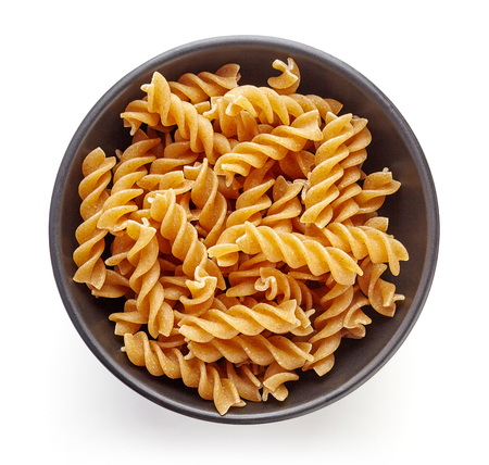 carbohydrates: spiral pasta in bowl, isolated on white background, top view Stock Photo