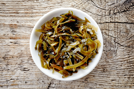 Bowl of sea kale on wooden background, top view 版權商用圖片