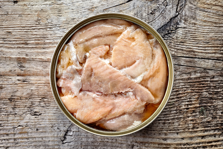 Open tin can, canned salmon, on wooden background, top view