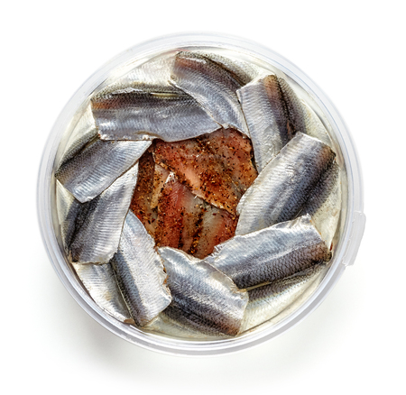 Bowl of anchovy fillets isolated on white background; top view