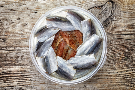 Bowl of anchovy fillets on wooden background; top view