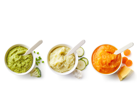 Green, yellow and orange baby puree in bowl isolated on white background, top view Imagens