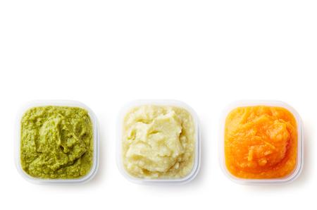 Purea di bambino verde, gialla ed arancio in recipienti di plastica isolati su fondo bianco, vista superiore