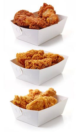 Fried breaded chicken in white cardboard boxes isolated on white background