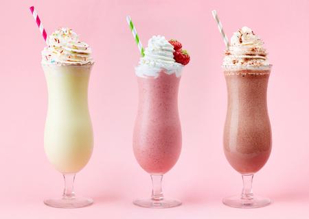 Strawberry, chocolate and vanilla milkshake with whipped cream on pink background 写真素材
