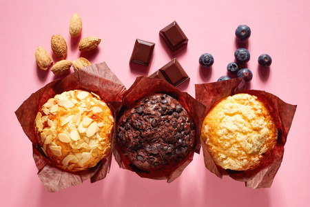 Assorted muffins in brown paper on pink background, top view