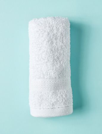 White spa towel on light blue background, top view