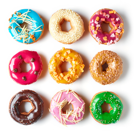 Various colorful donuts isolated on white background, top view