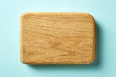 Wooden cutting board on blue background, top view