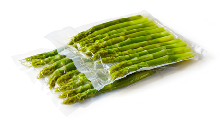 Fresh asparagus vacuum sealed rady for sous vide cooking, isolated on white background