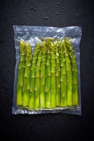 Fresh asparagus vacuum sealed ready for sous vide cooking, on black background, top view