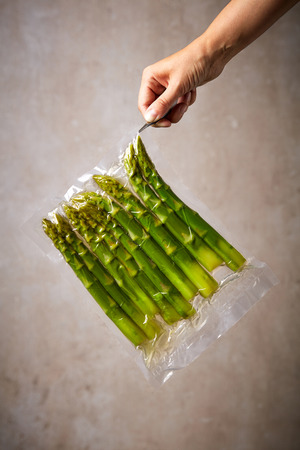 Hand with tweezers holding asparagus in sous vide bag, stone wall background