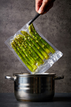 Hand holding fresh asparagus in sous vide bag over cooking pot
