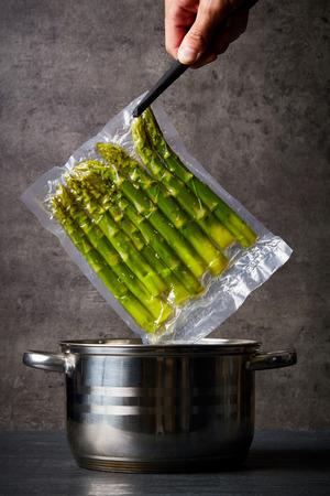 Hand met verse asperges in sous vide zak over kookpot Stockfoto
